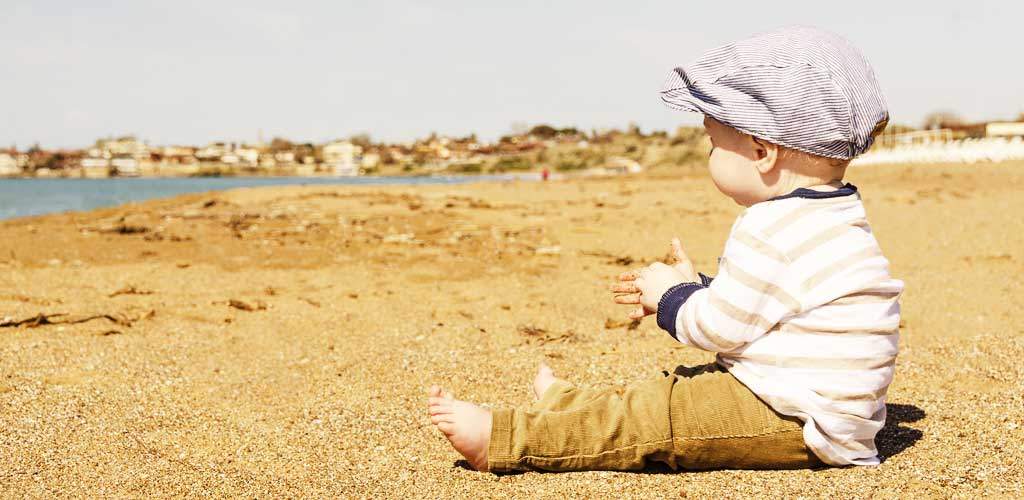 bébé à la mer sur le sable attend le repas